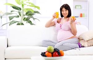 Pregnant woman drinking fruit juice and holding orange.