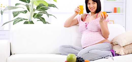 Pregnant woman drinking fruit juice and holding orange.