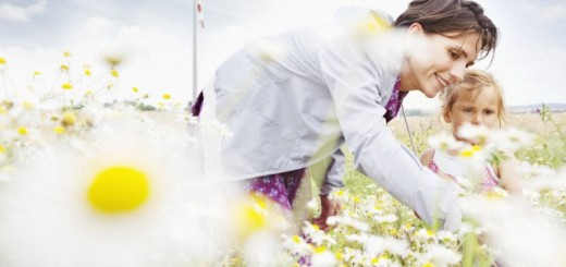 Mother picking daisies with daughter